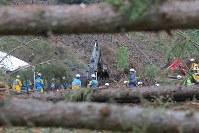 地震による大規模な土砂崩れが起き、大量の木や土砂に埋まった現場で安否不明者を捜索する消防隊員ら=北海道厚真町幌内で2018年9月9日午後2時40分、和田大典撮影