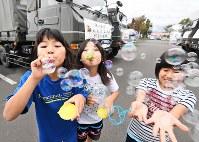 自衛隊の車が並ぶ駐車場でシャボン玉を飛ばす避難所の子どもたち。引率した「放課後子ども教室」のスタッフ、上道和恵さん(33)は「普段と違う生活で子ども達も疲労が溜まって来ているように見える。楽しく遊んで少しでもストレスをなくしてあげたい」と話した=北海道厚真町で2018年9月9日午後3時20分、山崎一輝撮影