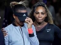 【女子シングルス決勝】試合後、サンバイザーで目元を隠す大坂なおみ(左)とハグするセリーナ・ウィリアムズ=AP