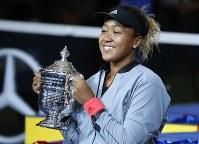 全米オープンで優勝し、トロフィーを手に笑顔を見せる大坂=AP