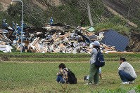A family looks on as rescue workers and other authorities search for people near a house that was hit by a landslide caused by an earthquake in the town of Atsuma, Hokkaido, on Sept. 7, 2018. (Mainichi)