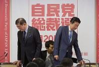 自民党総裁選の記者会見の冒頭で握手後、着席する安倍晋三首相(右)と石破茂元幹事長=党本部で2018年9月10日午前10時59分、川田雅浩撮影
