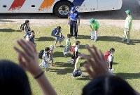 西日本豪雨で校舎が被災したため、市立玉島小に登校する市立箭田小の児童ら。手前は校舎から手を振って迎える玉島小の児童たち=岡山県倉敷市で2018年9月3日午前8時21分、平川義之撮影