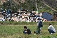 北海道胆振東部地震による土砂崩れで倒壊した家屋の捜索活動を見守る家族ら=北海道厚真町で撮影2018年9月7日午前11時47分、竹内幹撮影