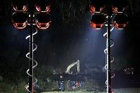 地震で土砂崩れが発生した現場(奧)で照明を照らし、夜通し安否不明者の捜索を続ける自衛隊や消防隊ら=北海道厚真町で2018年9月8日午後8時31分、和田大典撮影