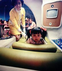 サンヨー館 健康カプセル内で不安そうな表情でリクライニングベッドに乗る女の子=1970年