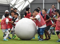 Local children roll a big ball together at a sports festival to mark the opening of a domed training field at J-Village in the town of Naraha, Fukushima Prefecture, on Sept. 8, 2018. (Mainichi)