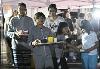 炊き出しのご飯を受け取って避難所に戻る家族ら=北海道厚真町で2018年9月11日午後6時42分、山崎一輝撮影