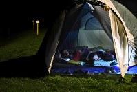 自宅近くのキャンプ場に張ったテントで寝る家族連れ。余震も心配して、倒れてくるものがないキャンプ場に就寝時のみ来ている=北海道千歳市で2018年9月10日午後8時半、山崎一輝撮影
