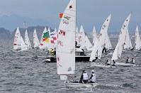 2020年東京五輪の初のテスト大会となるセーリングW杯の競技が始まり、江の島(左奥)沖に色々な国旗をあしらったヨットが走った=神奈川県・江の島沖で2018年9月11日午後0時6分、梅村直承撮影