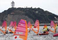 2020年東京五輪の初のテスト大会となるセーリングW杯の競技が始まり、江の島(奥)沖に色々な国旗をあしらったウィンドサーフィンが走った=神奈川県・江の島沖で2018年9月11日午後2時1分、梅村直承撮影