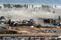 A tsunami triggered by the March 11, 2011 Great East Japan Earthquake is seen surging inland in Natori, Miyagi Prefecture, in the country's northeast. (Mainichi)