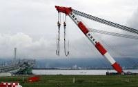 損傷した橋桁を撤去するための作業が続く連絡橋(左)=関西国際空港で2018年9月12日午後0時1分、幾島健太郎撮影