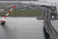 橋桁の撤去作業が始まった関西国際空港の連絡橋(右)。奥は関西国際空港=2018年9月12日午前11時12分、本社ヘリから小松雄介撮影
