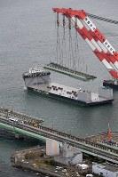 関西国際空港の連絡橋(手前)から撤去され、台船に積み込まれる破損した橋桁=2018年9月12日午後3時42分、本社ヘリから小松雄介撮影