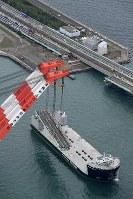 関西国際空港の連絡橋(奥)から撤去され、台船に積み込まれる破損した橋桁=2018年9月12日午後3時33分、本社ヘリから小松雄介撮影