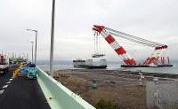 クレーン船でつり上げられ、台船に載せられる関西国際空港の連絡橋の損傷した橋桁=2018年9月12日午後3時29分、幾島健太郎撮影