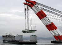 クレーン船でつり上げられ、台船に載せられる関西国際空港の連絡橋の損傷した橋桁=2018年9月12日午後3時28分、幾島健太郎撮影