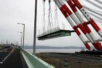 クレーン船でつり上げられる関西国際空港の連絡橋の損傷した橋桁=2018年9月12日午後1時42分、幾島健太郎撮影