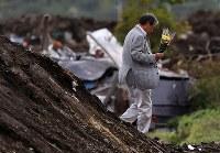 親族4人を亡くし、現場を訪れた千葉県市川市の中田毅さん(78)。「こんなにひどいとは。生前のことを思い出すと苦しくなる」と話し、倒壊した生家を回りながら花束を置いていった=北海道厚真町で2018年9月12日午後2時58分、貝塚太一撮影