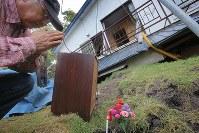 震度7の地震が襲った北海道厚真町では12日、犠牲者宅を訪れる人たちの姿があった。倒壊した家で中村ミヨさん(76)が亡くなった現場には花束が供えられ、近隣住民が線香を手向けた。衣類など使える物を取り出しに来た次男の忠雄さん(56)は、「ミヨさんはよくここで草刈りをしていたね」などと生前の姿を思い返し、手を合わせる住民たちに「母のためにありがとうございます」と礼を言っていた=北海道厚真町で2018年9月12日午後2時47分、和田大典撮影