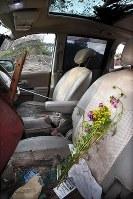 最大震度7を記録した大地震による土砂崩れで多くの人が亡くなった北海道厚真町吉野地区。残された車の助手席には花が手向けられていた=北海道厚真町で2018年9月12日午後3時11分、山崎一輝撮影