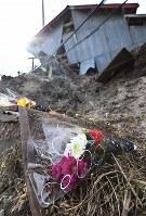 最大震度7を記録した大地震による土砂崩れで男性が亡くなった現場に手向けられた花束=北海道厚真町で2018年9月12日午後3時16分、山崎一輝撮影