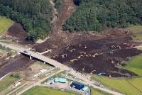 大規模な土砂崩れで川がせき止められた場所では重機での復旧作業が続いていた=北海道厚真町で2018年9月12日午前9時55分、本社機「希望」から梅村直承撮影