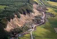 土砂崩れで多くの犠牲者が出た集落では道路の上の土砂が取り除かれていた=北海道厚真町で2018年9月12日午前10時5分、本社機「希望」から梅村直承撮影