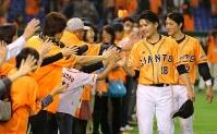 【巨人5-3中日】中日に勝利し、ファンとハイタッチする巨人・杉内俊哉(手前)と小林誠司=東京ドームで2014年4月18日、長谷川直亮撮影