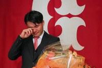 現役引退の記者会見を終え、チームメートの内海から花束を受け取り涙を流す杉内=東京都内のホテルで2018年9月12日午後4時35分、長谷川直亮撮影