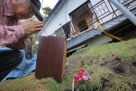 Tadao Nakamura, 56, prays on Sept. 12, 2018, for his mother Miyo, 76, who died after the Sept. 6 earthquake destroyed her house in the town of Atsuma, Hokkaido. (Mainichi)