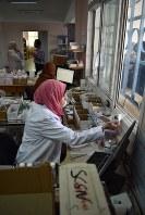 受け付けの窓越しにパレスチナ難民に薬を手渡す薬剤師=UNRWAのソフタウィ保健センターで2018年9月6日、高橋宗男撮影