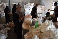 配給用のひよこ豆や砂糖などを仕分けするUNRWA臨時職員。難民を対象とした3カ月任期の雇用対策だが、10月以降制度が存続できるかは不透明だ=ガザ市近郊のビーチキャンプで2016年9月5日、高橋宗男撮影