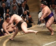 土俵際で踏みとどまる白鵬(左)。右は貴景勝=東京・両国国技館で2018年9月13日、丸山博撮影