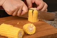 トウモロコシは3等分して芯から実をそぎ落とします=根岸基弘撮影