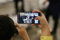 A visitor films a frozen tuna auction on a smartphone at Tsukiji fish market in Tokyo's Chuo Ward on Sept. 14, 2018. (Pool photo)