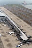 再開した第1ターミナル。奥は橋桁の撤去作業が進む連絡橋=関西国際空港で2018年9月14日午前9時2分、本社ヘリから望月亮一撮影