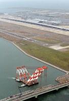 橋桁の撤去作業が進む連絡橋。奥は再開した第1ターミナル=関西国際空港で2018年9月14日午前9時、本社ヘリから望月亮一撮影
