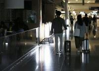 再開されたが、いまだに一部で停電が続く第1ターミナルを歩く旅行者たち=関西国際空港で2018年9月14日午前8時36分、小出洋平撮影