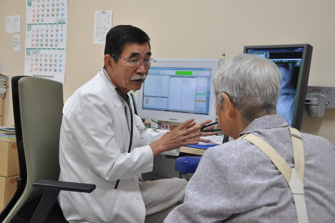 Doctor Shunji Sekine provides an explanation to a patient with a gesture at the Tsushima temporary clinic in the Fukushima Prefecture city of Nihonmatsu, on Sept. 11, 2018. (Mainichi)