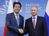 In this Sept. 10, 2018 photo, Japanese Prime Minister Shinzo Abe, left, and Russian President Vladimir Putin shake hands prior to their talks at the Eastern Economic Forum in Vladivostok, Russia. (Mikhail Metzel/TASS News Agency Pool Photo via AP)
