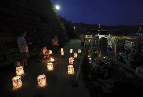 お盆に集まり、花壇の前で言葉を交わす遺族。犠牲になった行員を思い、「帰っておいで」と言いながら迎え火を焚いた。中央右は行員を模した男女が彫り込まれたモニュメント宮城県女川町で2018年8月13日、佐々木順一撮影