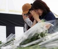 町役場前に設置された犠牲者追悼献花台に花束を供え、手を合わせる母子。防災無線で献花台設置を知り、歩いて訪れた。織田明美さん(52・写真右)は知り合いを震災で亡くし、「今でも信じられないが、その方と犠牲者全員への追悼をさせていただきました」と話した=北海道厚真町で2018年9月15日午後2時1分、貝塚太一撮影