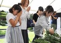 町役場前に設置された犠牲者追悼献花台に花束を供え、手を合わせる人たち=北海道厚真町で2018年9月15日午後1時16分、貝塚太一撮影