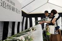 町役場前に設置された犠牲者追悼献花台に花束を供える家族連れ=北海道厚真町で2018年9月15日午後0時10分、貝塚太一撮影