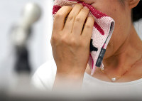 判決後の記者会見で涙をぬぐう大野輝民さんの妻佳奈子さん=大阪市北区で2018年6月28日、山田尚弘撮影