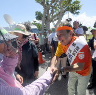 Candidate for Okinawa governor, Denny Tamaki, right, shakes hands with his supporters after the launch of his campaign in the village of Ie on a small Okinawa prefectural island on Sept. 13, 2018. (Mainichi)