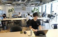 カフェゾーンで仕事をする金田謙祐さんの後ろにはキッチンスペース。窓に向いた席や、形が異なるソファもある=東京都港区のユーグレナで、田村佳子撮影