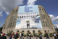 In this Sept. 12, 2018 file photo, people walk past under a banner showing North Korean leader Kim Jong Un, left, and South Korea President Moon Jae-in to wish for the successful inter-Korean summit at Seoul City Hall in Seoul, South Korea. (AP Photo/Ahn Young-joon, File)